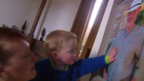 Baby Logan touches a photograph of his late father, Frank Lawlor. (9NEWS)