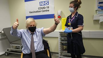 Britain's Prime Minister Boris Johnson gestures after receiving the first dose of AstraZeneca vaccine