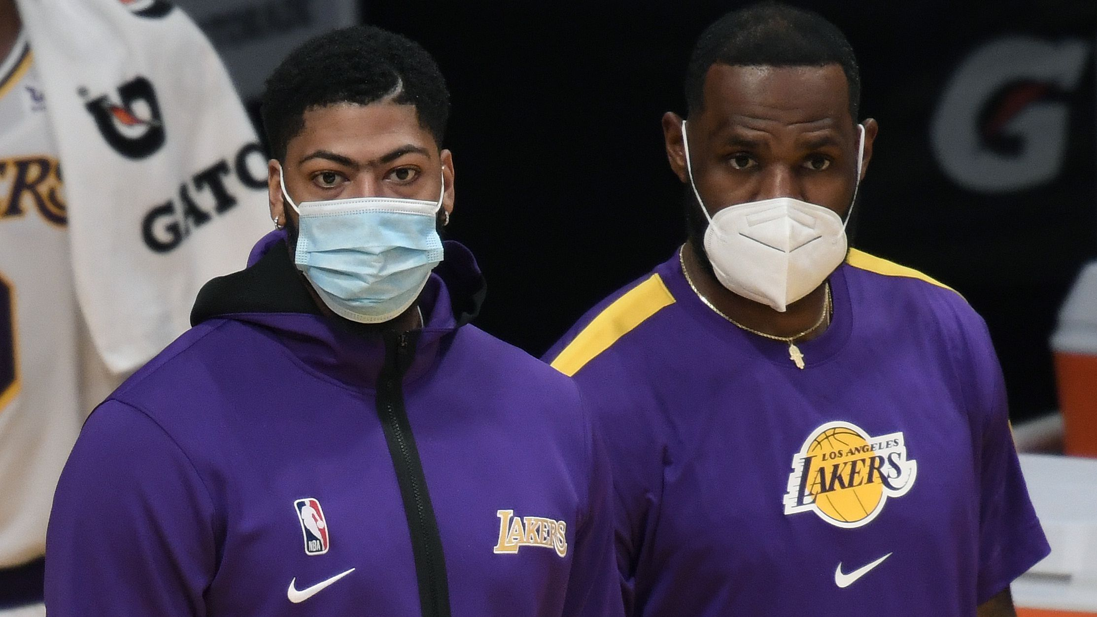 Anthony Davis and LeBron James of the Los Angeles Lakers watch a preseason game.