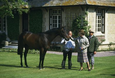 Queen Elizabeth II of Britain examines a horse at Le Quesnay horse farm near Deauville.