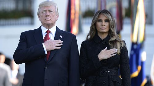 President Donald Trump and First Lady Melania Trump observe a minute silence at the White House. (AFP)