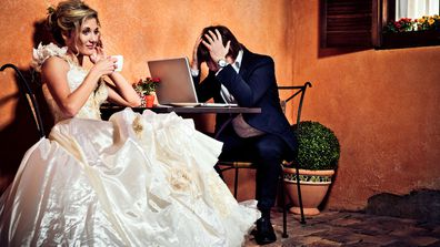 Stock image bride in wedding dress next to stressed out groom in front of computer