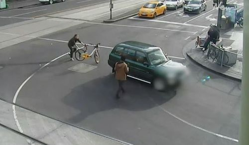 A man attempting to stop the driver threw his hire bicycle behind the vehicle. (Herald Sun)