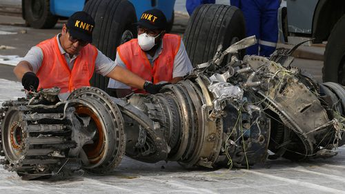 Officials inspect an engine recovered the crashed Lion Air jet in Jakarta.