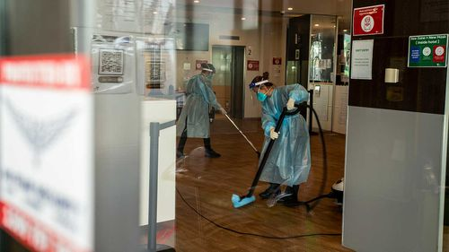 Cleaners are seen wearing full PPE while working at the disinfection of the Holiday Inn hotel.