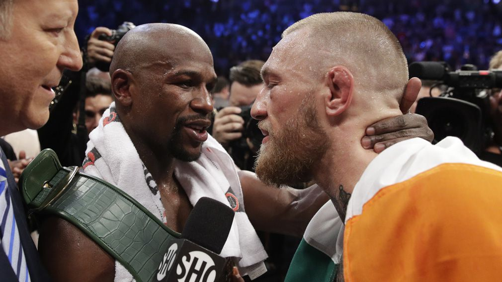Mayweather and McGregor share an embrace after the fight. (AAP)