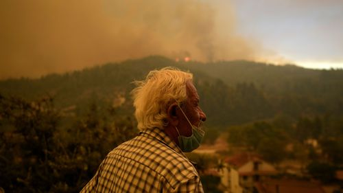 A local resident stands on a hill as flames approaching at Gouves village on the island of Evia, about 185 km north of Athens.