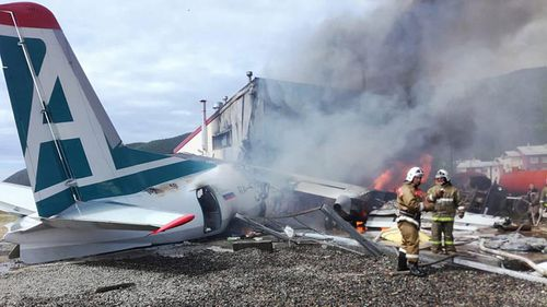Fire fighters at the site of the crash of an Antonov-24 passenger plane, which burst into flames after crash landing into a sewage treatment plant during an emergency landing.
