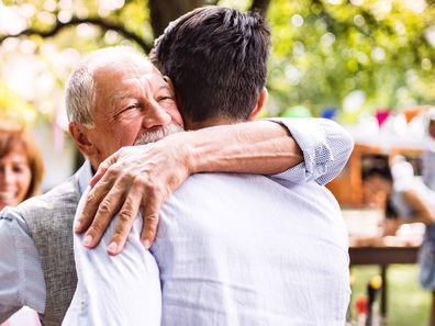 Grandfather hugging his adult grandson