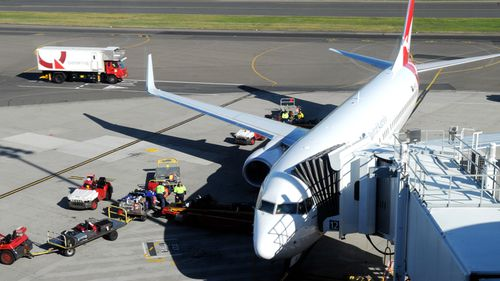 Baggage handlers unload luggage from a Qantas plane.