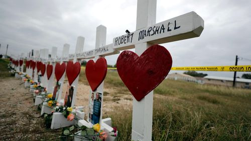 Crosses showing shooting victims names stand near the First Baptist Church. (AAP)