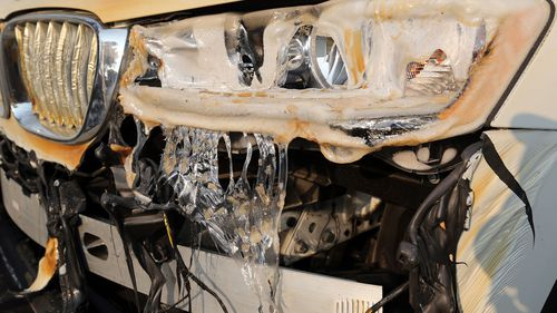 Glass and plastic melted from intense heat are seen on a car on Windermere Drive in the Point Dume area of Malibu.