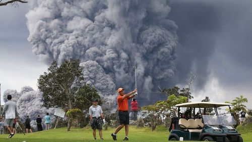 People play golf as an ash plume rises in the distance from the Kilauea volcano on Hawaii's Big Island on May 15, 2018 in Hawaii Volcanoes National Park, Hawaii. (Getty)
