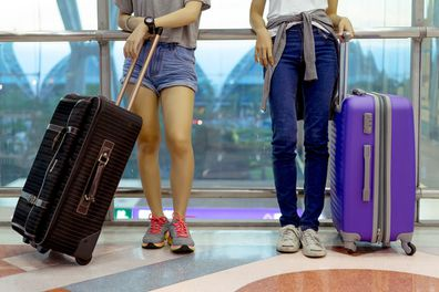 Girl holding suitcase ahead of flight.