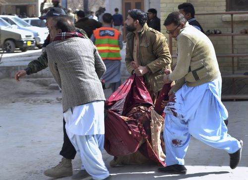 A paramilitary soldier and volunteers rescue an injured women following a suicide attack on a church in Quetta, Pakistan. (AAP)