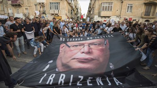 A banner with the photo of the Malta police commissioner Lawrence Cutajar is laid on the floor outside the Malta Police Headquarters during a spontaneous protest which followed a rally to honor Daphne Caruana Galizia. (AAP)