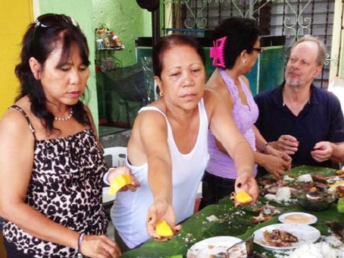 Paddock (far right) shares a meal with Marilou Danley's family in the Philippines. (Supplied)