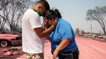 Dora Negrete (Right) is consoled consoled by her son, Hector Rocha (Left) , after seeing their destroyed mobile home in Talent, Oregon.