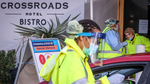 Medical staff at a pop-up COVID-19 testing clinic, perform tests on drivers in the Sydney suburb of Casula.