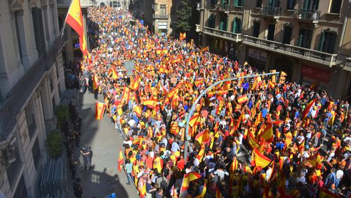 Ten of thousands of flag-waving demonstrators packed central Barcelona to rally against plans by separatist leaders to declare Catalonia independent. (AAP)