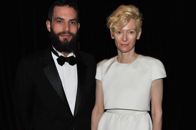 """Tilda may have twins with partner John Byrne, but they both openly enjoy romantic relationships with other people! Enter current toy boy Sandro Kopp. <br/>Speaking of her erm, unique living arrangement Tilda told <i>The New York Post</i>""""What is true is that John and I live here with our children and Santo sometimes here with us... and we travel the world together. We are all a family."""" <br/><br/>She added: """"I've been painted as a benign eccentric who'se living here while some guy's shagging his sweetheart. Why would I do that?""""<br/><br/>Bizarre, indeed. <br/>"""