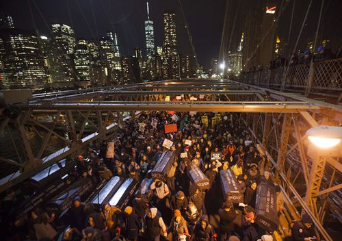 A group of protesters rallying against a grand jury's decision not to indict the police officer involved in the death of Eric Garner occupies the eastbound traffic lanes of the Brooklyn Bridge in the early morning hours of December 4, 2014.