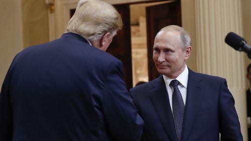 Presidents Donald Trump and Vladimir Putin shake hands. (AAP)