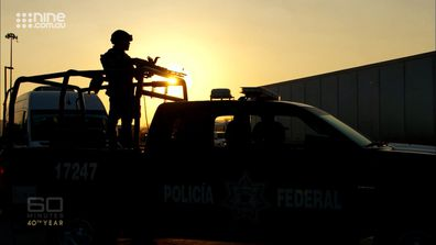 A soldier mans a machine gun as a cavalcade escorting Tom Steinfort and the 60 Minutes team speeds through streets in Mexico.