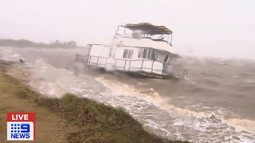 A houseboat washed ashore and stranded in waters off Queensland.