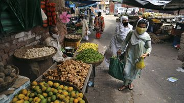 People wearing face masks as a precaution against the coronavirus walk after buying vegetables at market in Jammu, India.