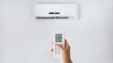 A person holding the remote for an air conditioning unit
