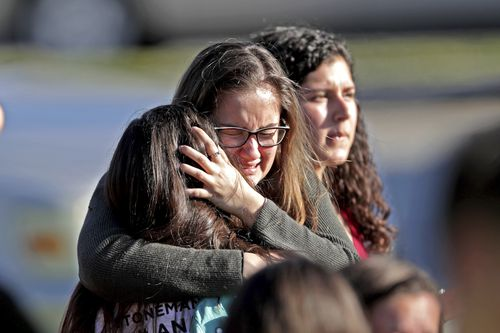 Students released from the lockdown embrace following the shooting. (AAP)