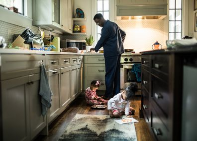 Father cooking breakfast for daughters in kitchen