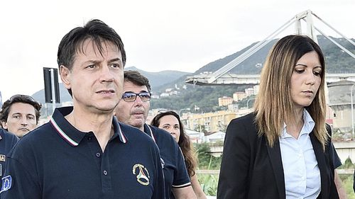 Italian Prime Minister Giuseppe Conte, left, visits the site of the disaster at Genoa.