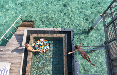 Floating breakfast tray in luxury hotel pool in the Maldives, overwater bungalow