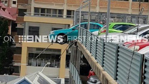 Car dangles over edge of high-rise car park at Brisbane hospital