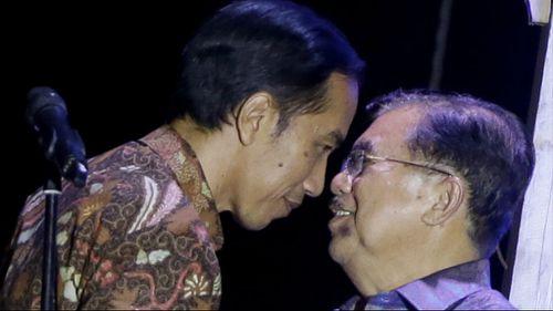 Indonesian president-elect Joko Widodo congratulates his running mate Jusuf Kalla. (AAP)
