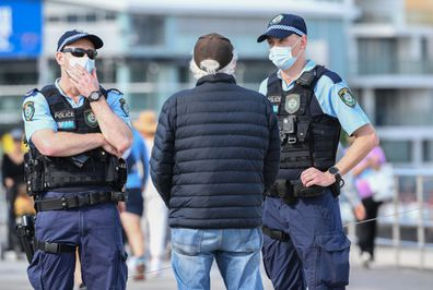 New South Wales police officers talk to locals on the beach promenade as part of their high profile compliance patrols at Bondi Beach on August 10, 2021.