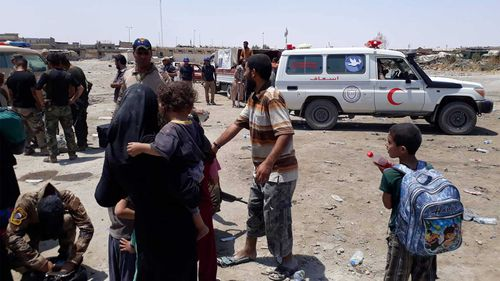 Mosul residents near a Red Crescent vehicle. (Owen Holdaway)
