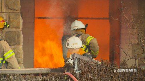 The brush fence of the Norwood home also caught fire. (9NEWS)