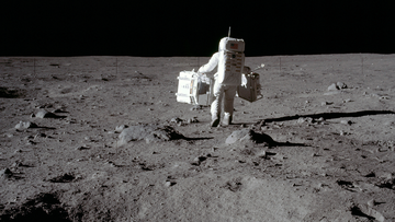 In this July 20, 1969 photo made available by NASA, lunar module pilot Buzz Aldrin carries a seismic experiments package in his left hand and the Laser Ranging Retroreflector to the deployment area on the surface of the moon at Tranquility Base.  (Neil Armstrong/NASA via AP)
