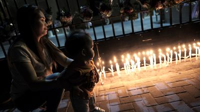 A woman lights a candle at a make-shift memorial for victims of the deadly Bastille Day attack