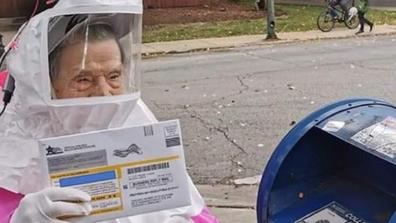 Elderly woman wears hazmat suit to vote in US election.