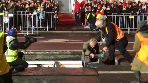 Hundreds anxiously watched on a drizzly Sunday night as the 73-year-old was dug up from Macquarie Street in the heart of the city. Picture: 9NEWS