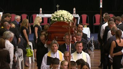Mourners were solemn as Hughes' coffin was carried out by family and friends. (9NEWS)