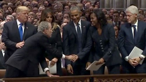 George W Bush hands a small item to Michelle Obama before the funeral for his father, George HW Bush.