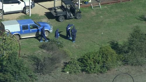 Forensic crews found two firearms at the scene. (9NEWS)