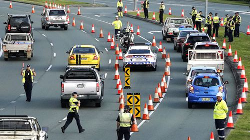 Motorists are stopped at a checkpoint on the Gold Coast Highway at Coolangatta on the Queensland/NSW border border , Thursday, March 26, 2020.