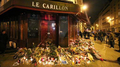 Mourners have left flowers outside the Le Carillon theatre, one of the restaurants attacked by terrorists. (Getty)