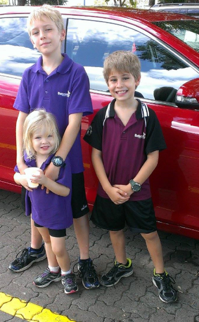 Leah children standing in front of car